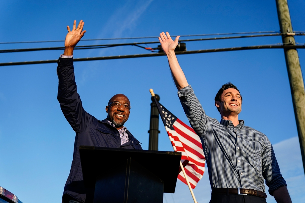 Georgia Democratic candidates for U.S. Senate Raphael Warnock, left, and Jon Ossoff, right, gesture toward a crowd during a campaign rally on Sunday, Nov. 15, 2020, in Marietta, Ga. (AP Photo/Brynn Anderson)