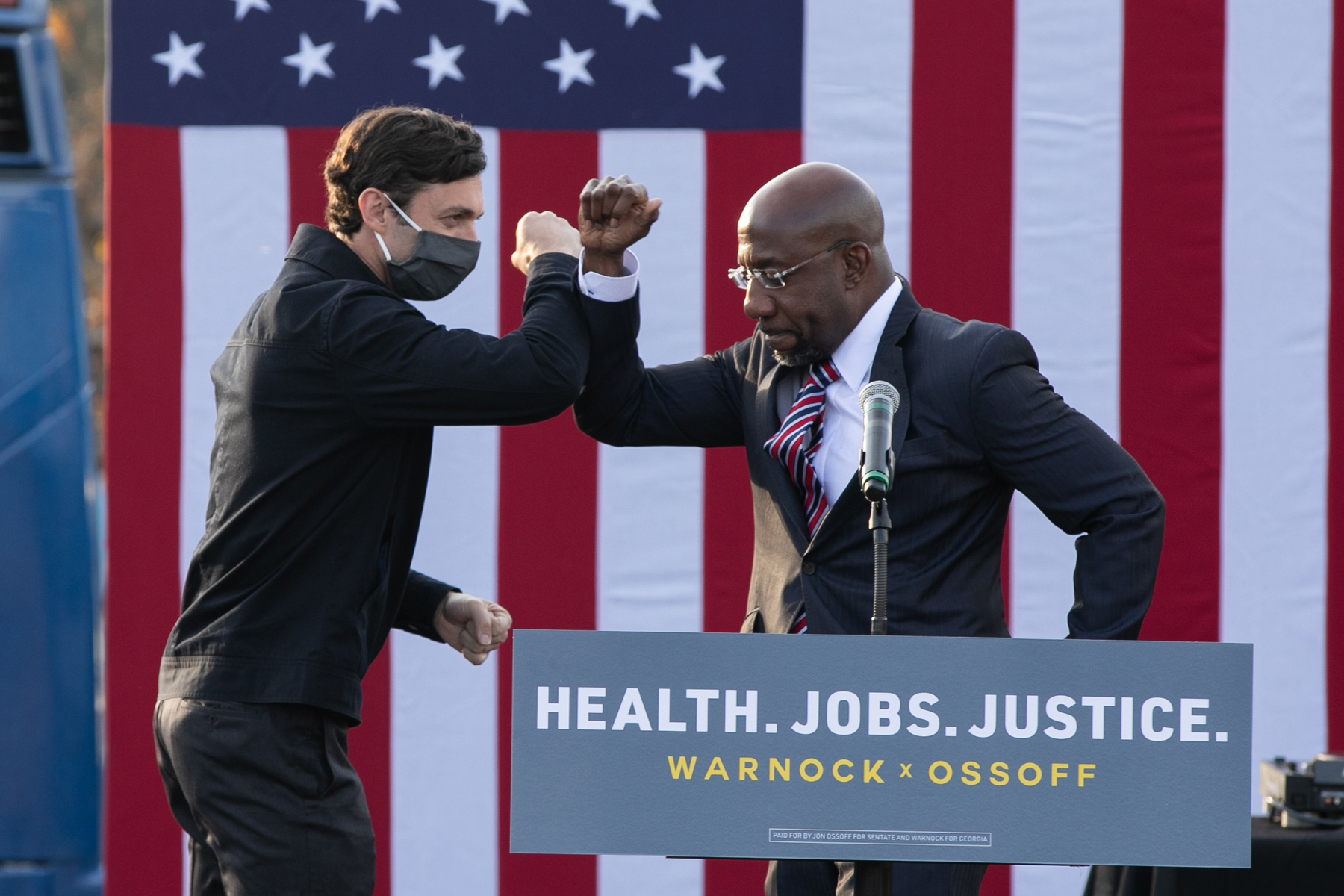 """STONECREST, GA - DECEMBER 28: Georgia Democratic Senate candidates Raphael Warnock (R) and Jon Ossoff (L) bump elbows during a """"It's Time to Vote"""" drive-in rally on December 28, 2020 in Stonecrest, Georgia. With a week until the January 5th runoff election that will determine control of the Senate, candidates continue to campaign throughout Georgia. (Photo by Jessica McGowan/Getty Images)"""