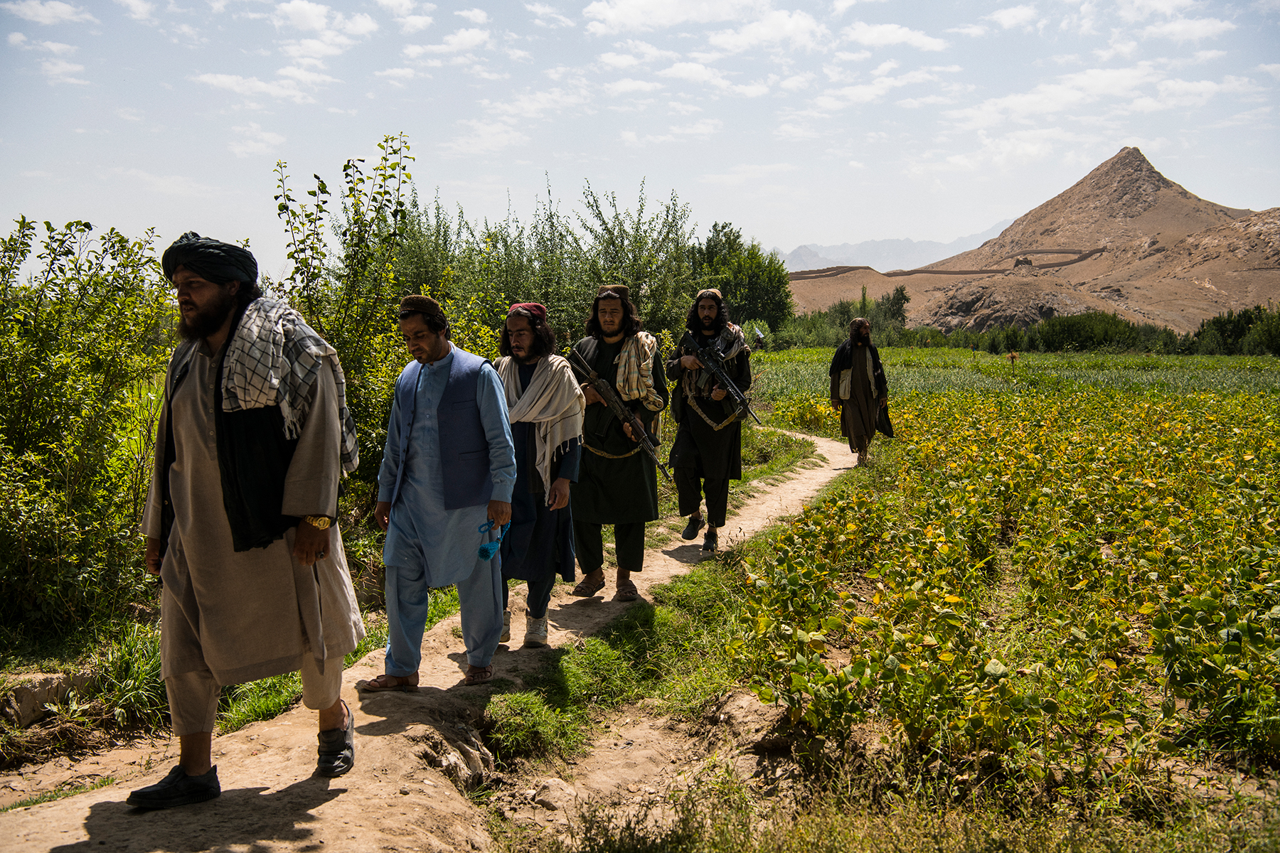 Local Taliban commander Tawakul leads fighters and bodyguards after an interview with American journalist Jason Motlagh in an apple orchard in the Taliban-controlled village of Qala Amir, Tangi Valley, Wardak province.The Tangi Valley and it's numerous villages, including Qala Amir, pictured, in Sayedabad district, Wardak province, has been under the control of the Taliban for several years following the withdrawal of American forces who occupied a small base just outside Qala Amir and is, since American forces curtailed their use of air power and special forces raids as agreed in the February 29 Doha Agreement with the Taliban, as much at peace as it has been probably since the insurgency began in the mid-2000s. The Tangi Valley saw extremely heavy fighting in the years that control was contested, but, once the U.S. withdrew from Tangi in 2014 and Afghan government forces were unable to hold it the only way it could be threatened was through night raids and air strikes, which occurred especially regularly in 2018 and 2019 as the Americans attempted to pressure the Taliban at the negotiating table. Wardak province, which neighbours Kabul to the southwest, has been a particularly violent province since then. Now, the majority of the province is under the control of the Taliban, with the government holding on to the capital, Maidan Shahr, some district centres and nominally, Highway 1 which passes lengthways through the province between Kabul and Ghazni province.