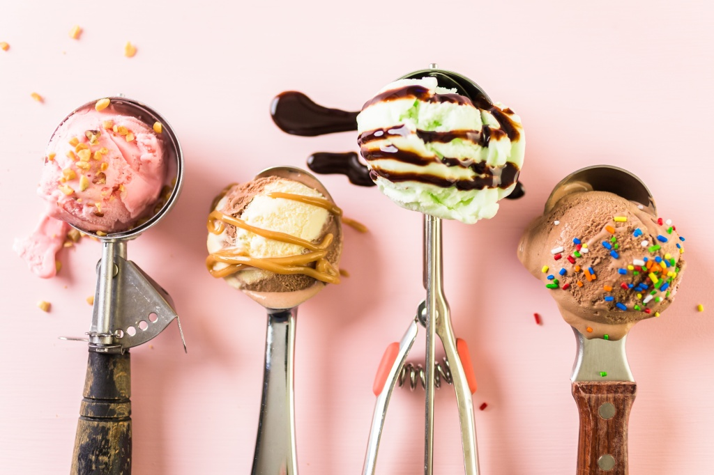 Variety of metal ice cream scoops with different ice cream and toppings on pink background.