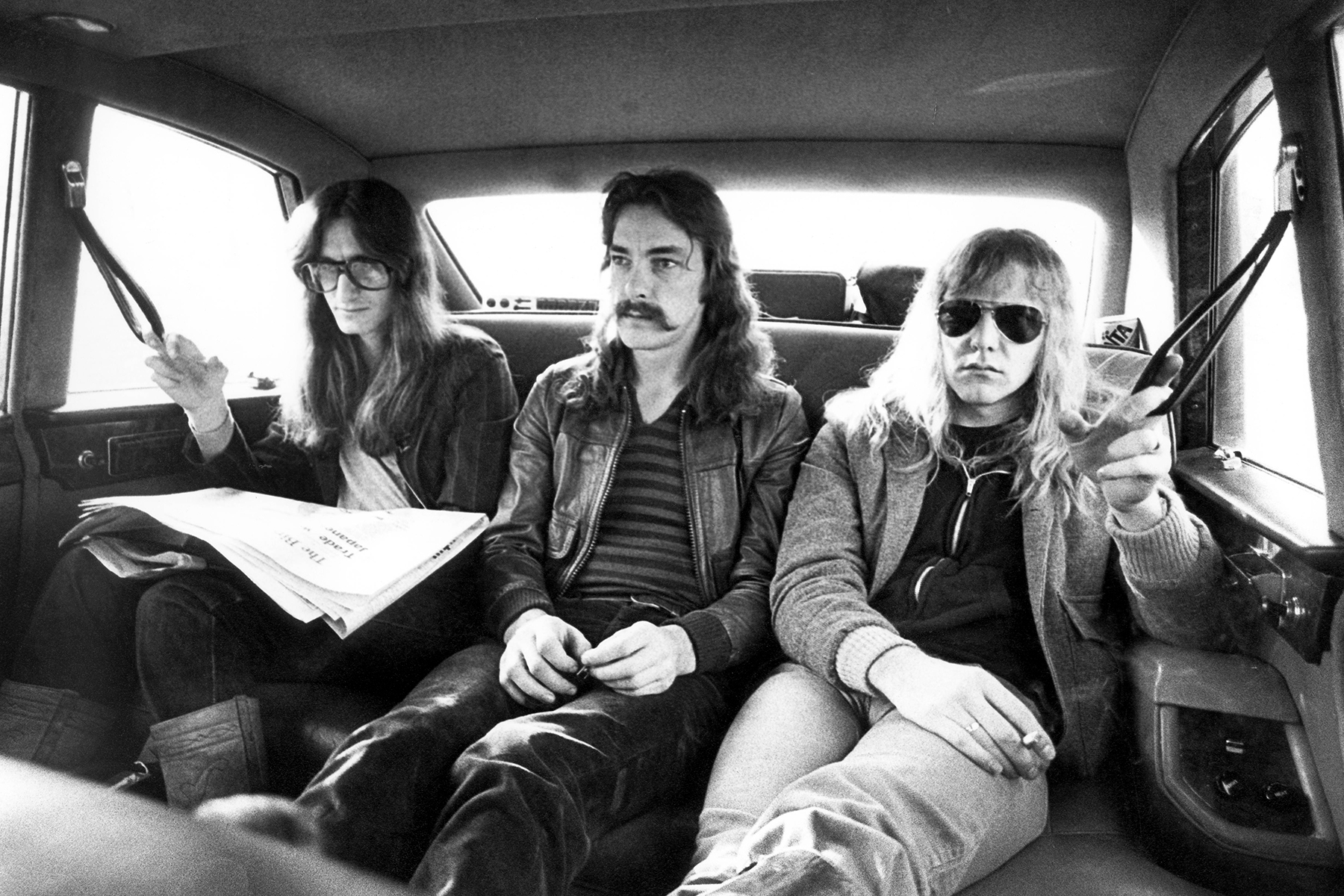 UNITED KINGDOM - FEBRUARY 12: BIRMINGHAM Photo of Neil PEART and RUSH and Geddy LEE and Alex LIFESON, Geddy Lee, Neil Peart, Alex Lifeson - posed, group shot, sitting in car during A Farewell To Kings tour (Photo by Fin Costello/Redferns)
