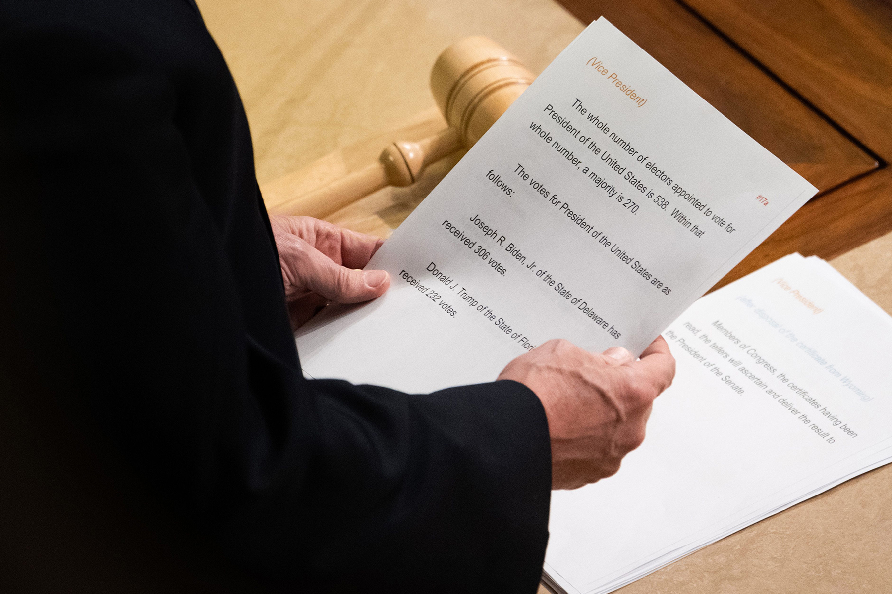 US Vice President Mike Pence reads a sheet of paper with the final electoral vote counts declaring Joe Biden as the next US President during a joint session of Congress to count the electoral votes for President, at the US Capitol in Washington, DC, January 7, 2021. - US lawmakers formally certified on January 7, Joe Biden as the winner of the presidential election -- clearing the way for his inauguration on January 20. Republican Vice President Mike Pence certified the Electoral College count of 306 electors in favor of the Democrat against 232 in favor of outgoing Republican President Donald Trump. The tally followed a joint session of the House and Senate that was interrupted by supporters of the president who stormed the US Capitol, bringing violence and mayhem to the seat of government. (Photo by SAUL LOEB / AFP) (Photo by SAUL LOEB/AFP via Getty Images)