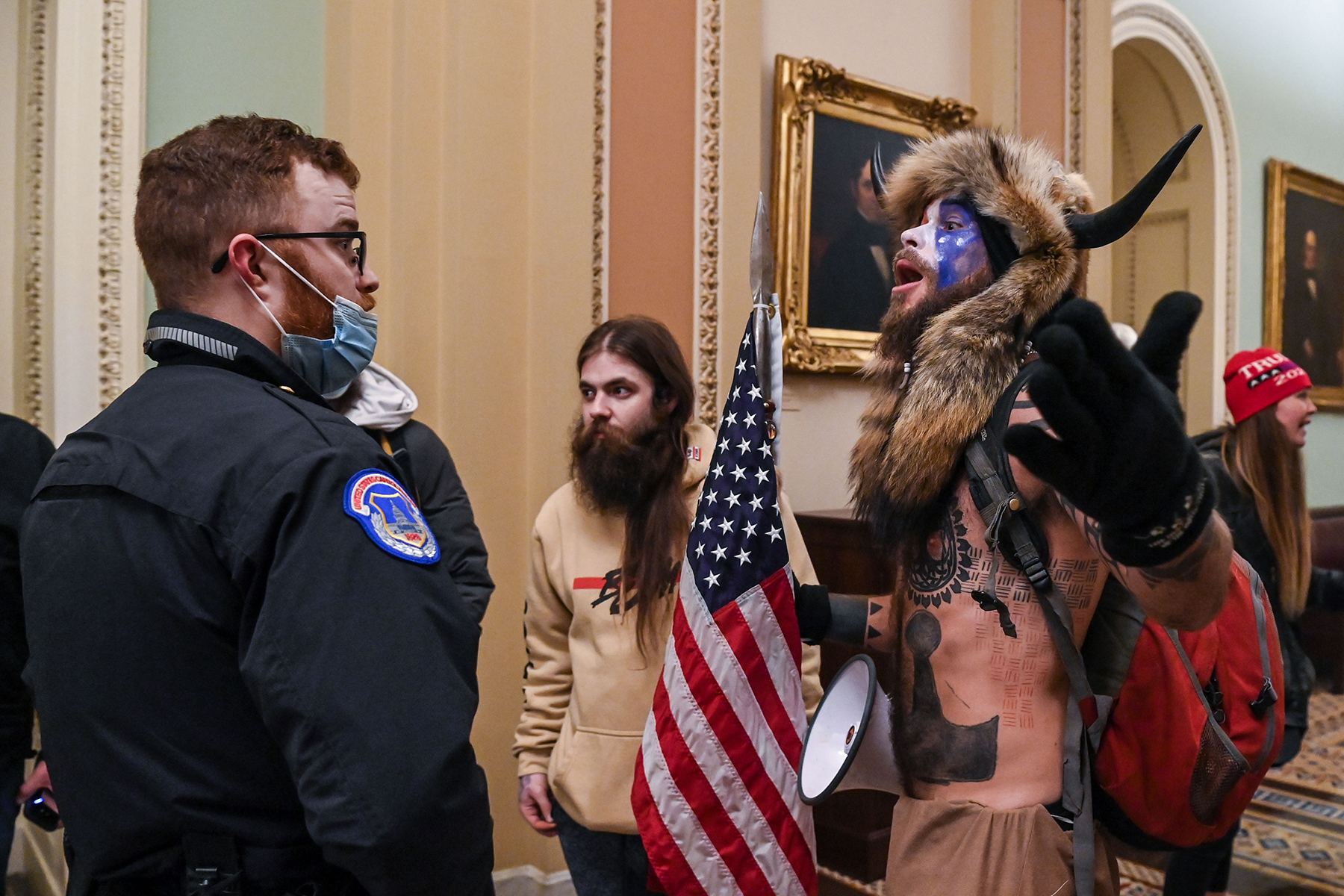 US Capitol police officers try to stop supporters of US President Donald Trump, including Jake Angeli (R), a QAnon supporter known for his painted face and horned hat, to enter the Capitol on January 6, 2021, in Washington, DC. - Demonstrators breeched security and entered the Capitol as Congress debated the a 2020 presidential election Electoral Vote Certification. (Photo by Saul LOEB / AFP) (Photo by SAUL LOEB/AFP via Getty Images)