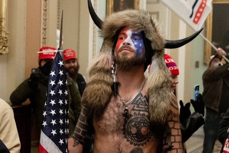 Supporters of US President Donald Trump, including Jake Angeli, a QAnon supporter known for his painted face and horned hat, protest in the US Capitol on January 6, 2021, in Washington, DC. - Demonstrators breeched security and entered the Capitol as Congress debated the a 2020 presidential election Electoral Vote Certification. (Photo by SAUL LOEB / AFP) (Photo by SAUL LOEB/AFP via Getty Images)