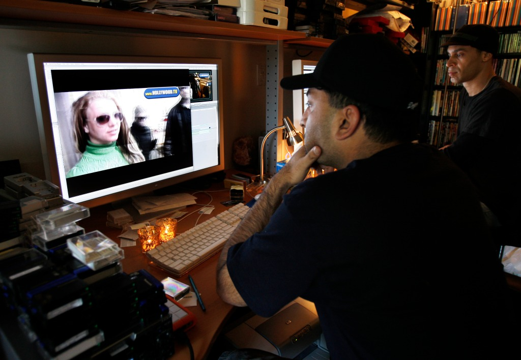 Sheeraz Hasan, founder and CEO of Hollywood.TV, left, edits a video clip of Britney Spears in his office in Beverly Hills, Calif., Tuesday, March 25, 2008. The photographers that trail Britney Spears day and night now share in a growing edge of her spotlight. As swarming tactics changed the rules of the Spears chase, police and deputies are responding with equal aggression. One splashy paparazzi newcomer drives a bright yellow Lambroghini. And another paparazzo was even dating Spears. (AP Photo/Kevork Djansezian)