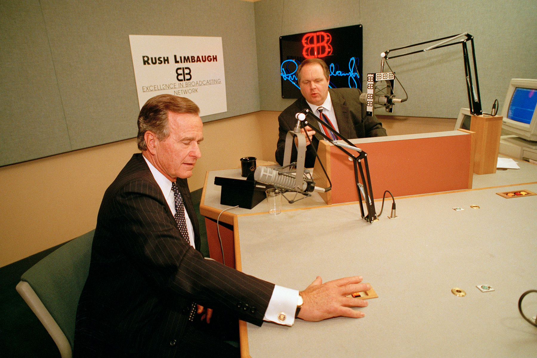 President George Bush talks with conservative radio host Rush Limbaugh at WABC studios in New York City, Sept. 1992. (AP Photo/J. Scott Applewhite)