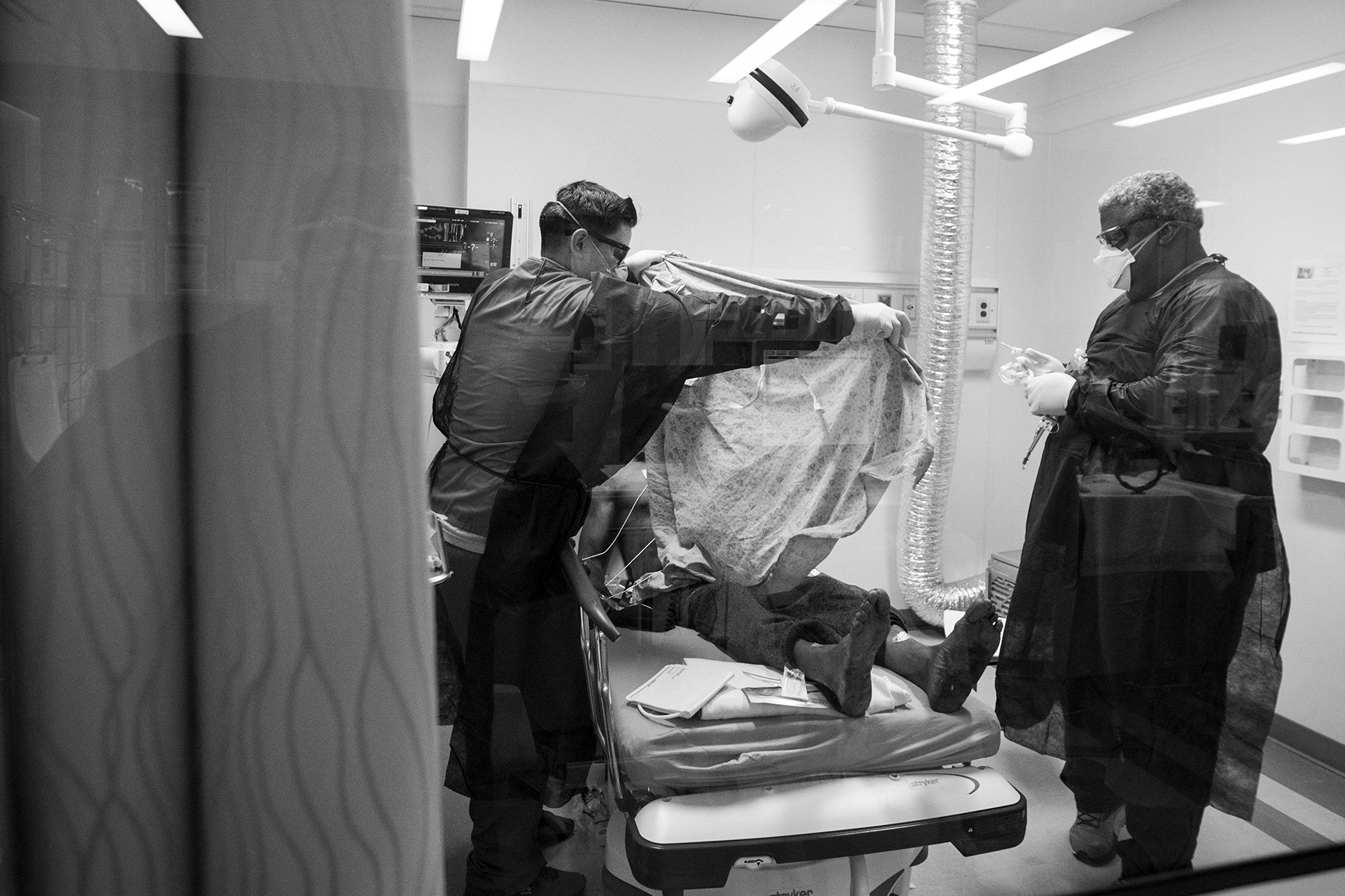 LOS ANGELES, CA - APRIL 24: Christopher Prado, EMT, left, and Jesse Lynwood, ED RN, right, work with a patient in the Emergency Department at Martin Luther King, Jr., Community Hospital on Thursday, April 23, 2020 in the Willowbrook neighborhood located in South Los Angeles, CA. The medical team suspects he is covid-19 positive and they are gowned up and putting a taking precautions. Christopher, left. is putting a gown on the patient. (Francine Orr/ Los Angeles Times via Getty Images)
