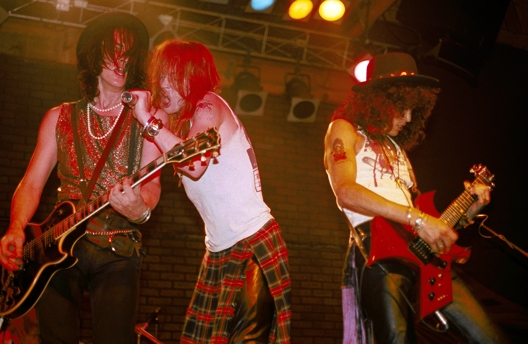 """LOS ANGELES - JUNE 6: (L-R) Izzy Stradlin, Axl Rose and Slash of the rock band 'Guns n' Roses' perform onstage at the Troubadour with the """"Appettite for Destruction"""" lineup together for the first time on June 6, 1985 in Los Angeles, California. (Photo by Marc S Canter/Michael Ochs Archives/Getty Images)"""