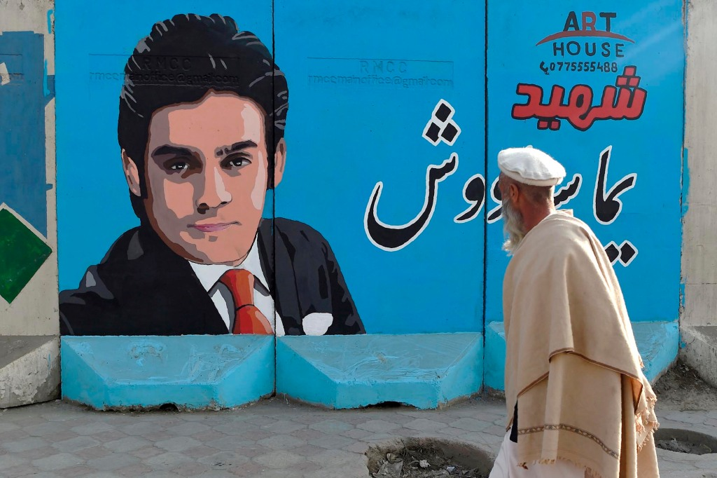 In this photo taken on January 19, 2021, a man walks past a barrier wall painted with an image of former Afghan Tolo TV presenter Yama Siawash, who was killed in a bomb attack on November 7, 2020, along a roadside in Kabul. - Journalists, religious scholars, activists and judges have all been targeted in a recent wave of political assassinations that has spread panic across Afghanistan and forced many into hiding -- with some even fleeing the country. (Photo by WAKIL KOHSAR / AFP) / TO GO WITH AFGHANISTAN-CONFLICT-KILLINGS,FOCUS BY JAY DESHMUKH AND USMAN SHARIFI (Photo by WAKIL KOHSAR/AFP via Getty Images)