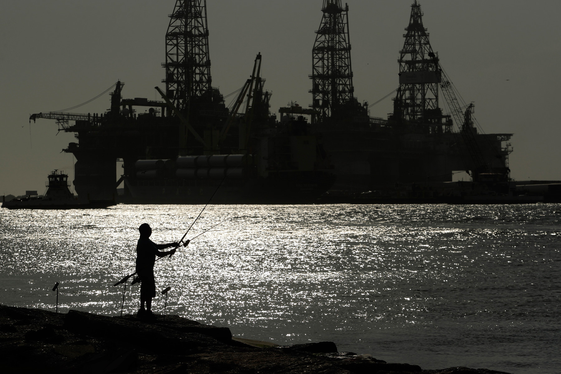 A man wear a face mark as he fishes near docked oil drilling platforms, Friday, May 8, 2020, in Port Aransas, Texas. Texas' stay-at-home orders due to the COVID-19 pandemic have expired and Texas Gov. Greg Abbott has eased restrictions on many businesses, churches, state parks and beaches. (AP Photo/Eric Gay)