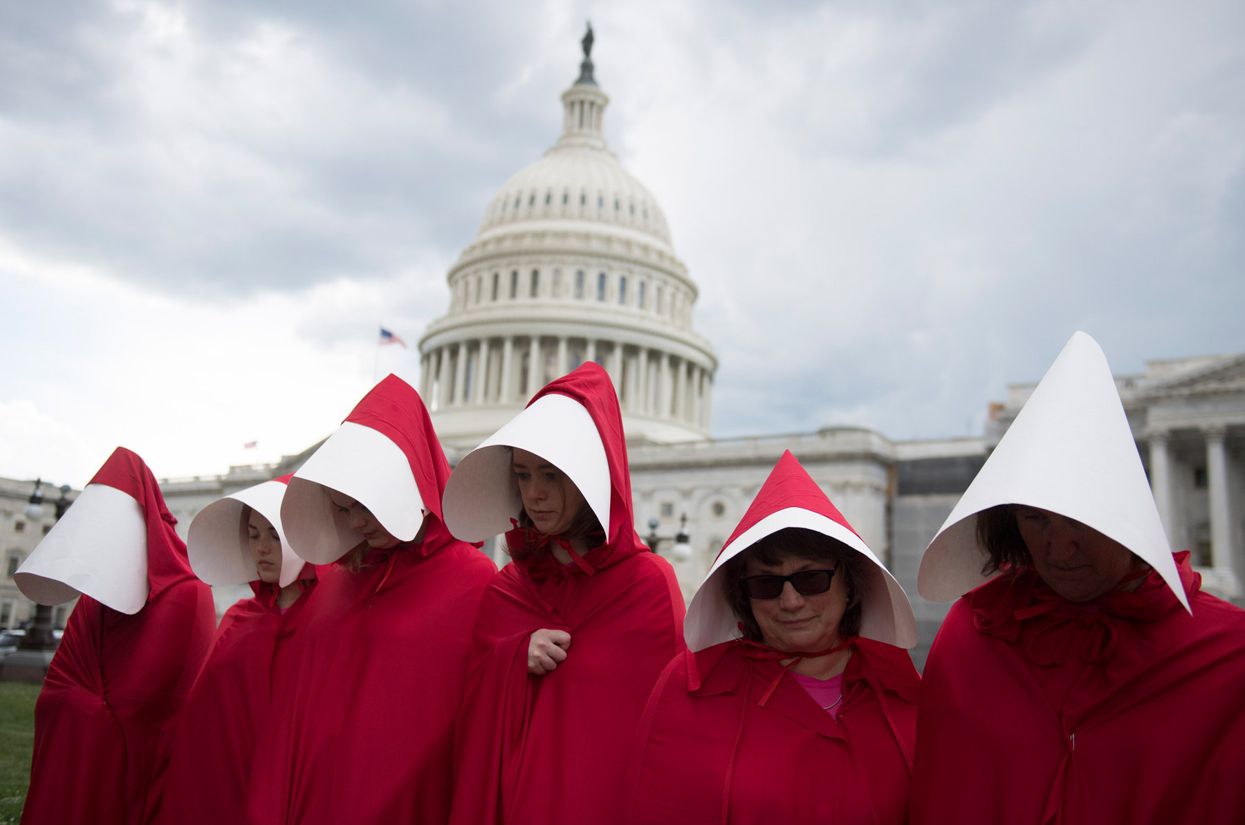 """Supporters of Planned Parenthood dressed as characters from """"The Handmaid's Tale,"""" hold a rally as they protest the US Senate Republicans' healthcare bill outside the US Capitol in Washington, DC, June 27, 2017. / AFP PHOTO / SAUL LOEB (Photo credit should read SAUL LOEB/AFP via Getty Images)"""