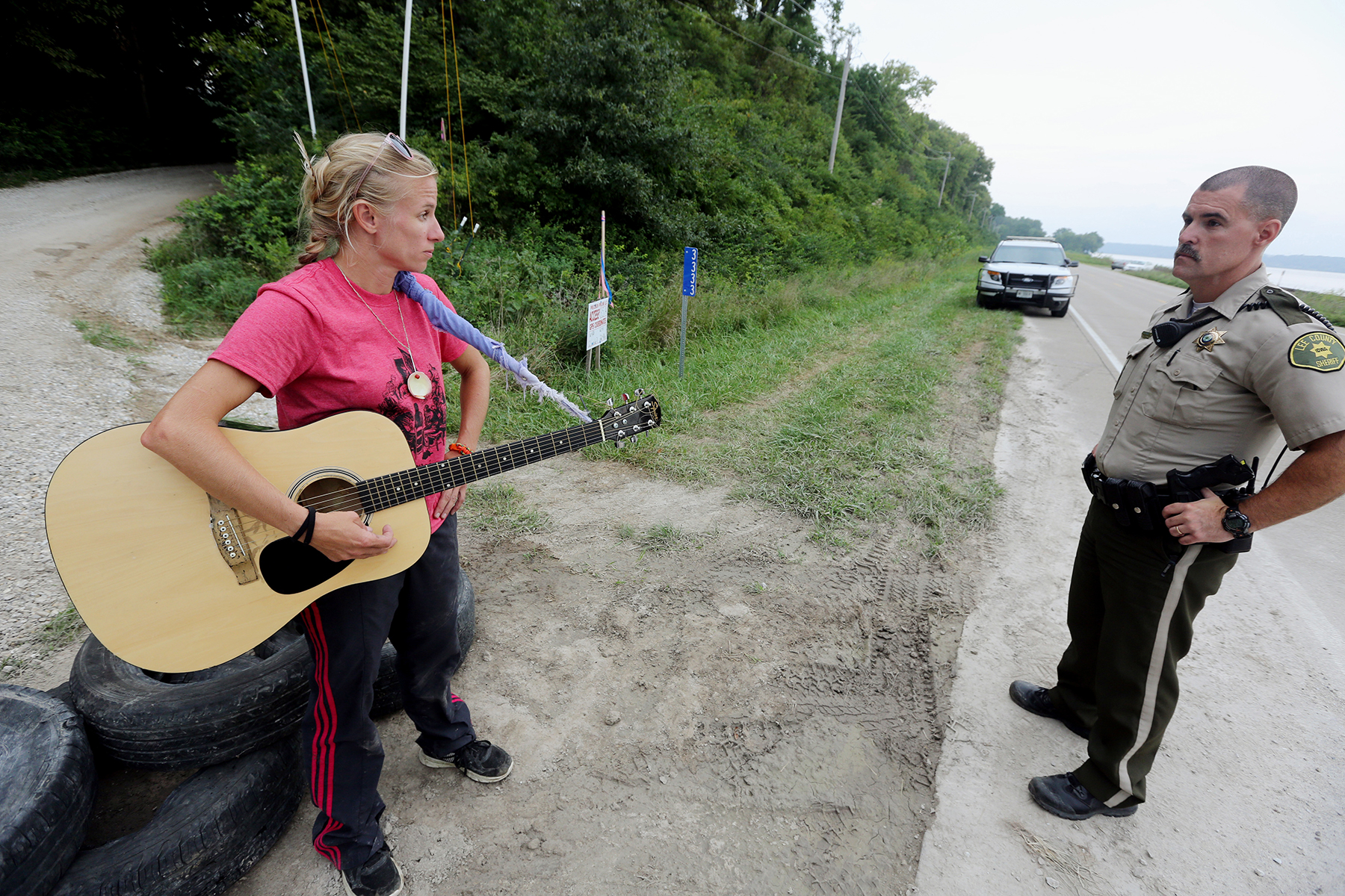 Activist Jessica Reznicek, talks with Lee County Sheriff's Deputy Steve Sproul while conducting a personal occupation and protesting the Bakken pipeline, Tuesday Aug. 30, 2016 at a pipeline construction site, along the Mississippi River Road near Keokuk, Iowa. Reznicek, a Des Moines Catholic Workers group member, was later taken into custody at about noon Tuesday by the Lee County Sheriff's Department. (John Lovretta/The Hawk Eye via AP)