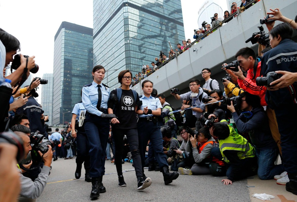 2CYC991 Singer and actress Denise Ho is taken away by policewomen from an area previously blocked by pro-democracy supporters, outside the government headquarters in Hong Kong, December 11, 2014. Hong Kong authorities started on Thursday clearing the main pro-democracy protest site that has choked roads into the city's most economically and politically important district for more than two months as part of a campaign to demand free elections. REUTERS/Tyrone Siu (CHINA - Tags: CIVIL UNREST ENTERTAINMENT POLITICS BUSINESS TPX IMAGES OF THE DAY)