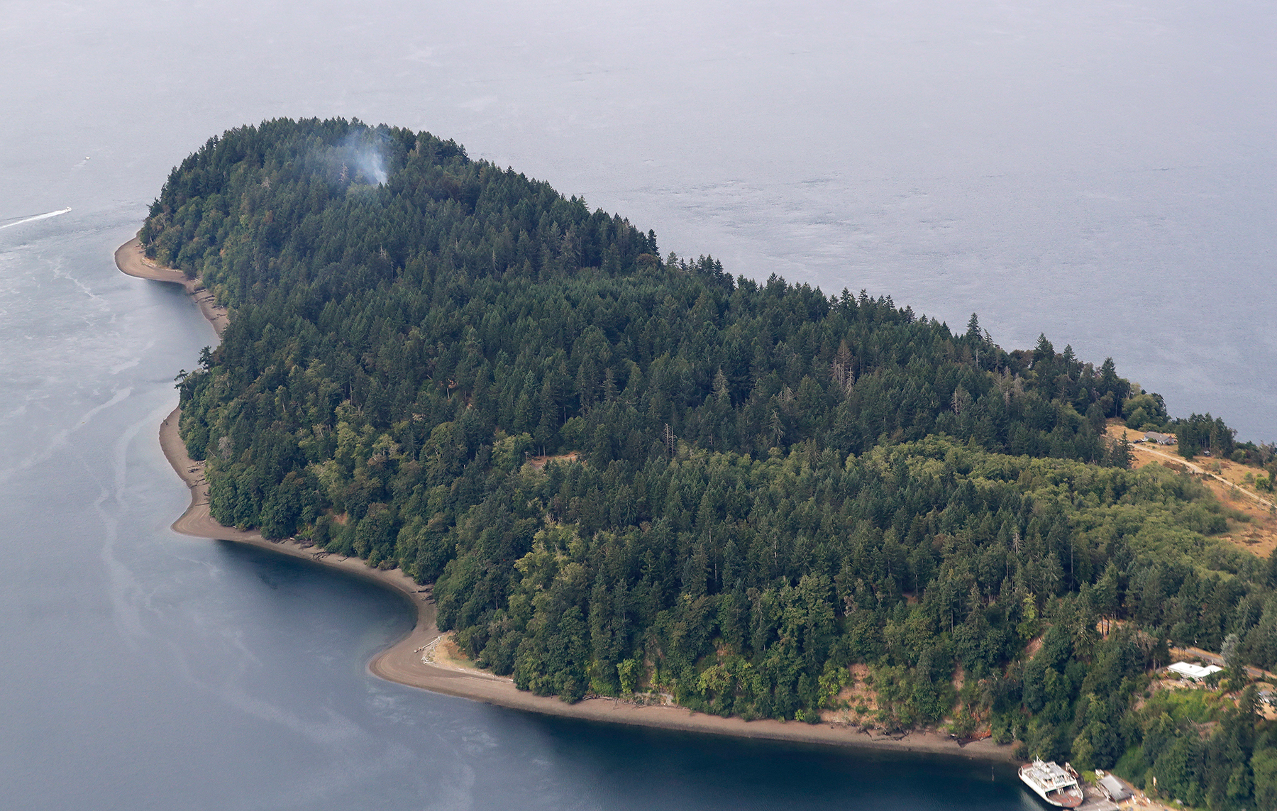Smoke rises from the site on Ketron Island in Washington state where an Horizon Air turboprop plane crashed Friday after it was stolen from Sea-Tac International Airport as seen from the air, Saturday, Aug. 11, 2018, near Steilacoom, Wash. Investigators were working to find out how an airline employee stole the plane Friday and crashed it after being chased by military jets that were quickly scrambled to intercept the aircraft. (AP Photo/Ted S. Warren)