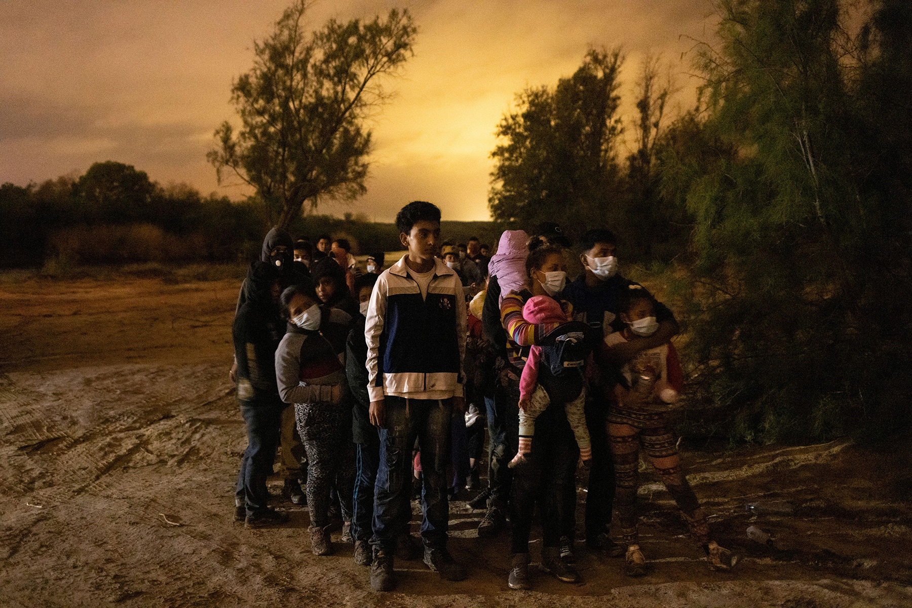2FNA8A7 Asylum seeking migrants from Central America line up to be escorted to the main road by the Texas Army National Guard after crossing the Rio Grande river into the United States from Mexico, in Roma, Texas, U.S., May 15, 2021. REUTERS/Adrees Latif