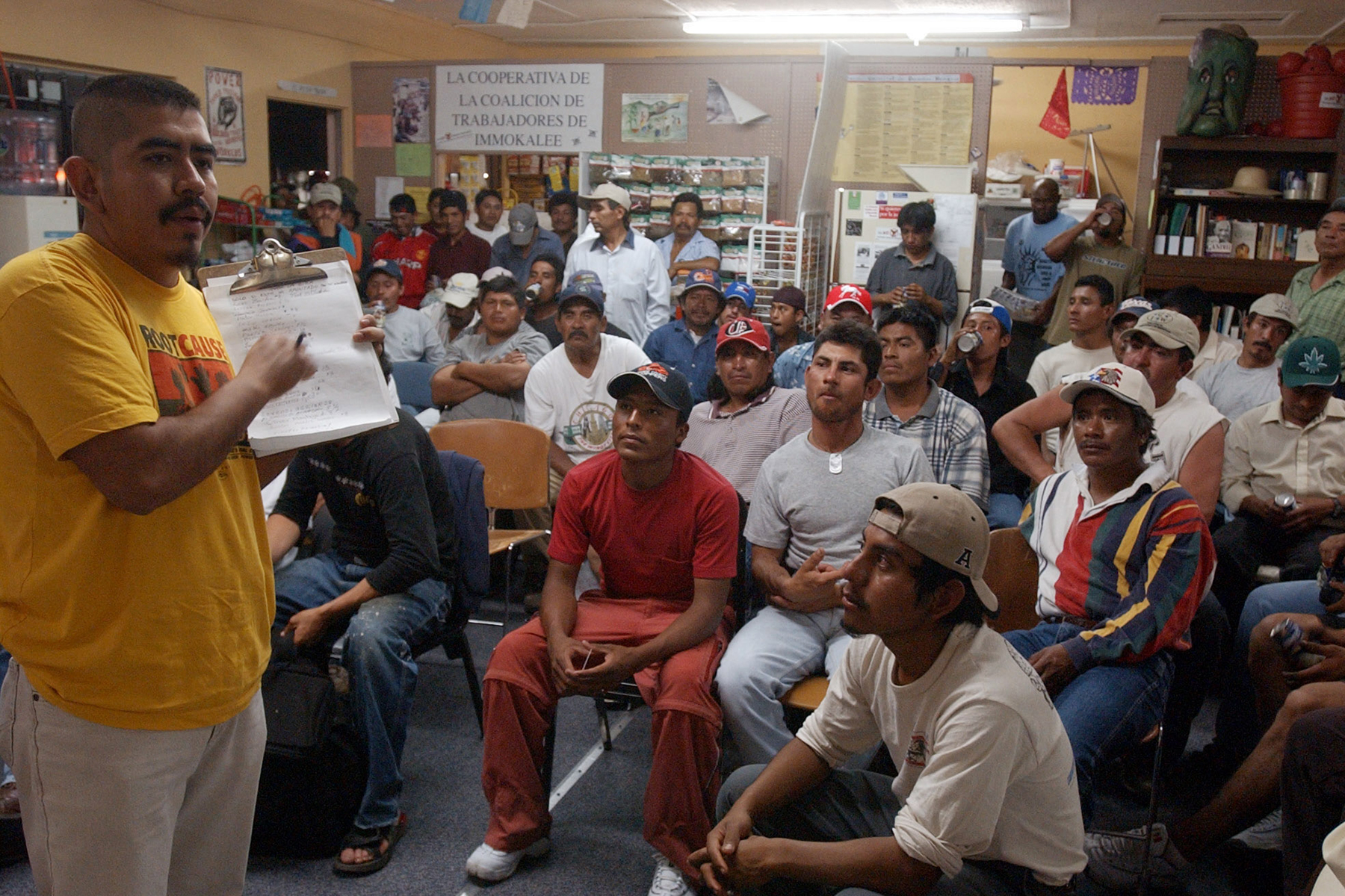 Lucas Benitez, left, conducts the weekly farmworkers meeting in Immokalee, Fla. Wednesday, Feb. 11, 2004 after the workers had spend the day picking crops in the nearby fields. (AP Photo/J.Pat Carter)