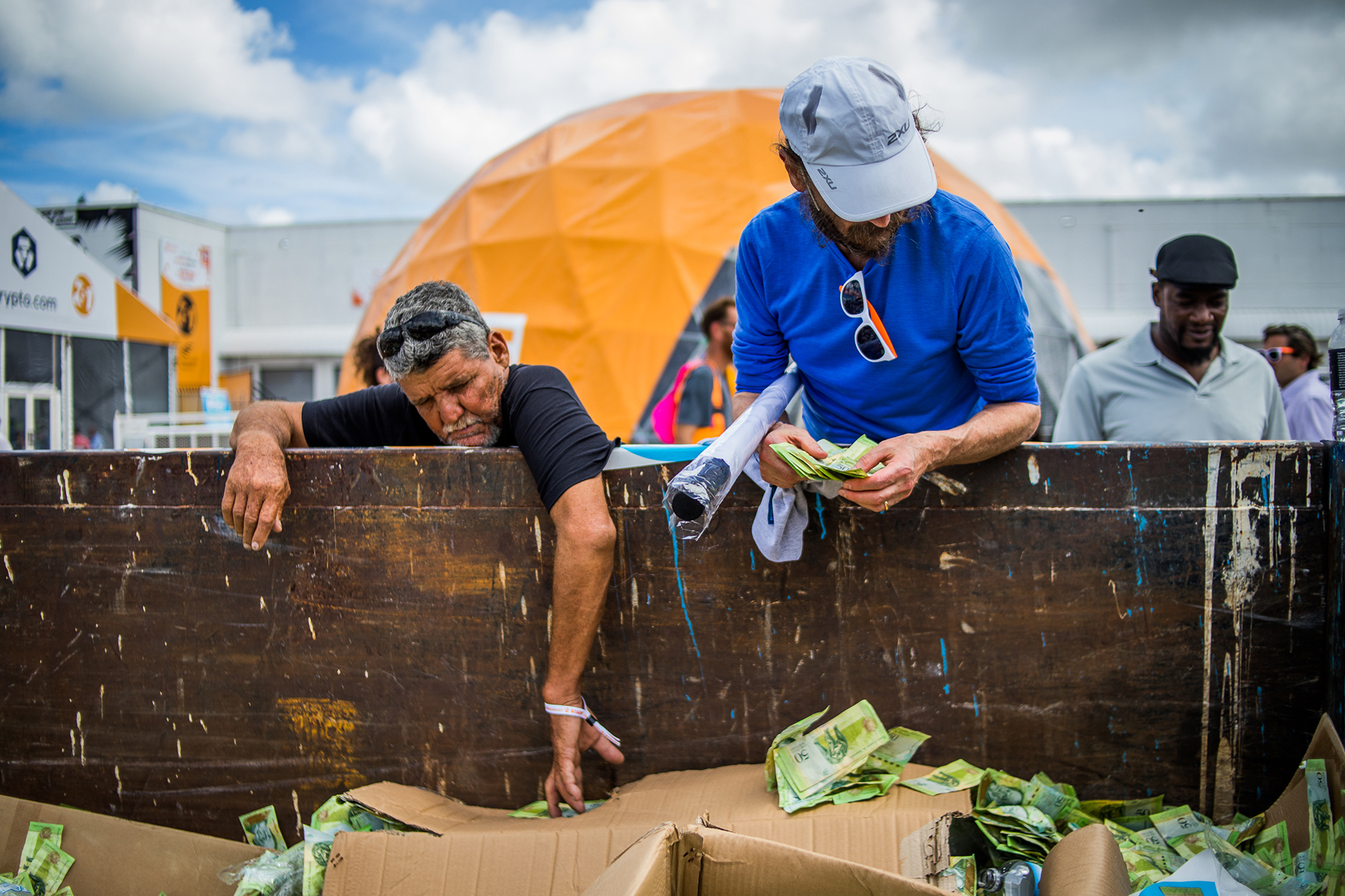 Festival attendees reach into a dumpster filled with Venezuelan Bolivars.