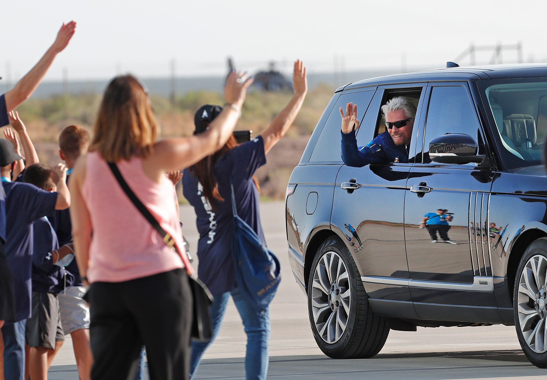 Virgin Galactic founder Richard Branson waves to school children while heading to board the rocket plane that will fly him to space from Spaceport America near Truth or Consequences, New Mexico, Sunday, July 11, 2021. (AP Photo/Andres Leighton)