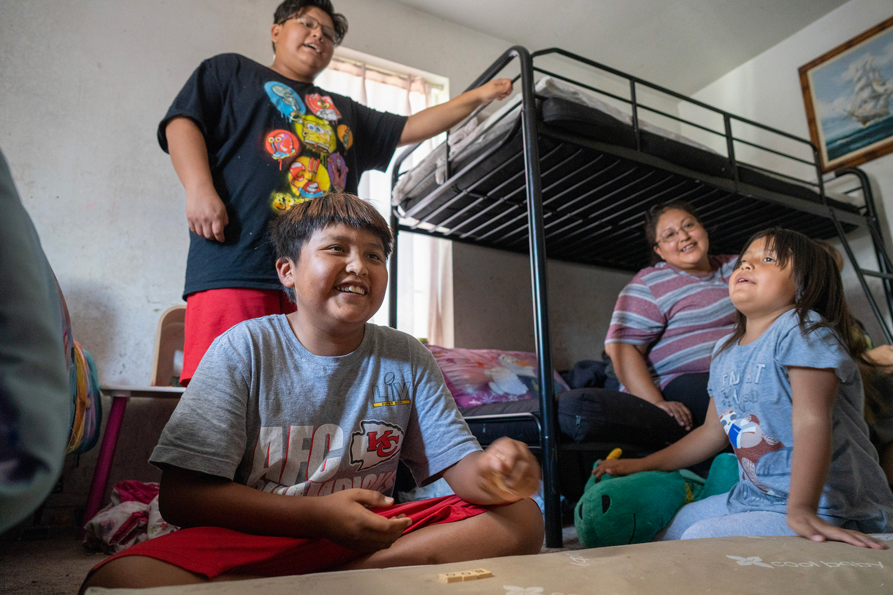 Carter Mariano plays word games with his family in a bedroom of their Shiprock home.