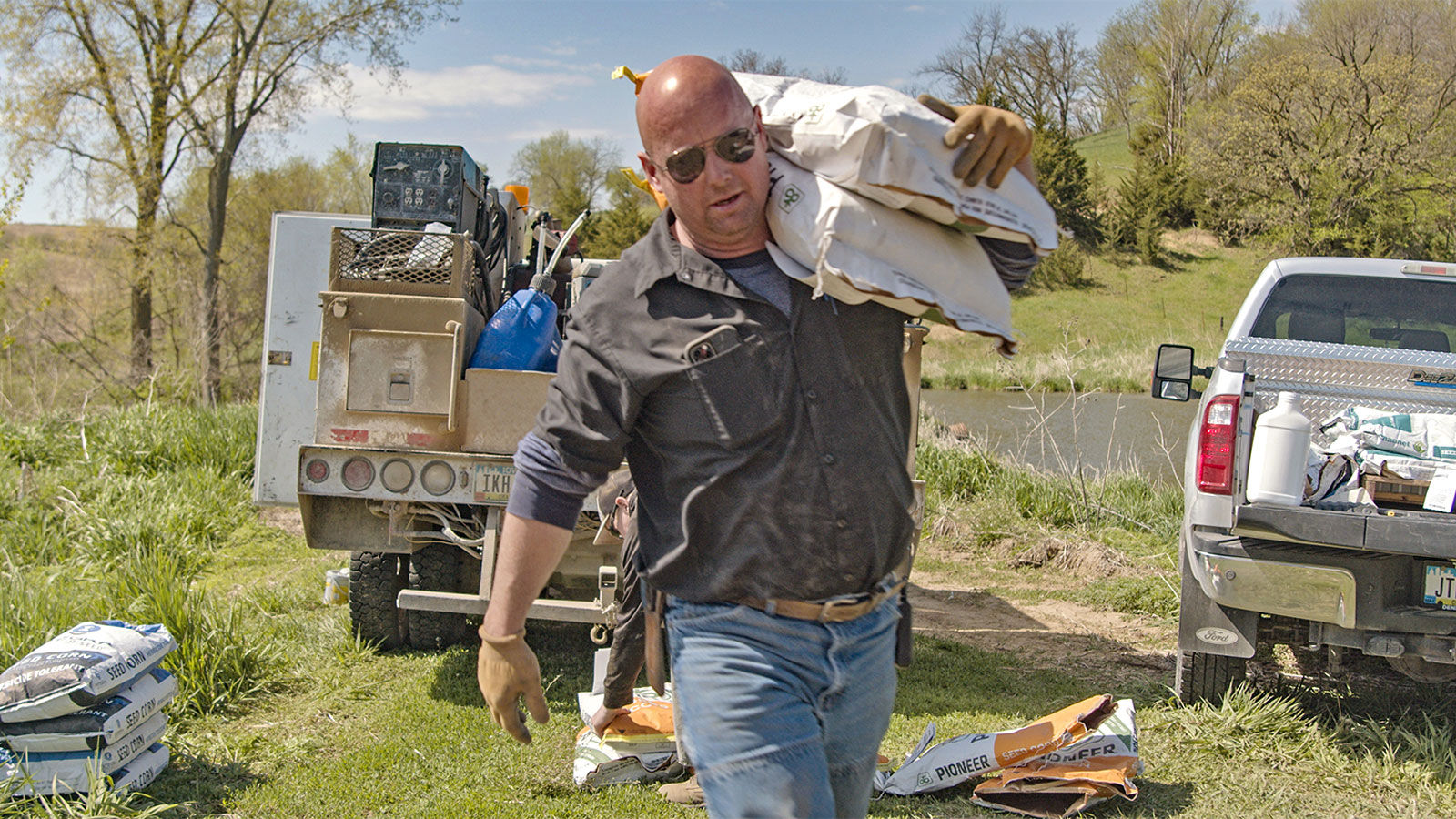 Kelly Garrett carries supplies on his 7,000-acre farm in Iowa. He has made nearly $150,000 partnering with corporations to offset planet-warming emissions by capturing additional carbon in his farm's soil.