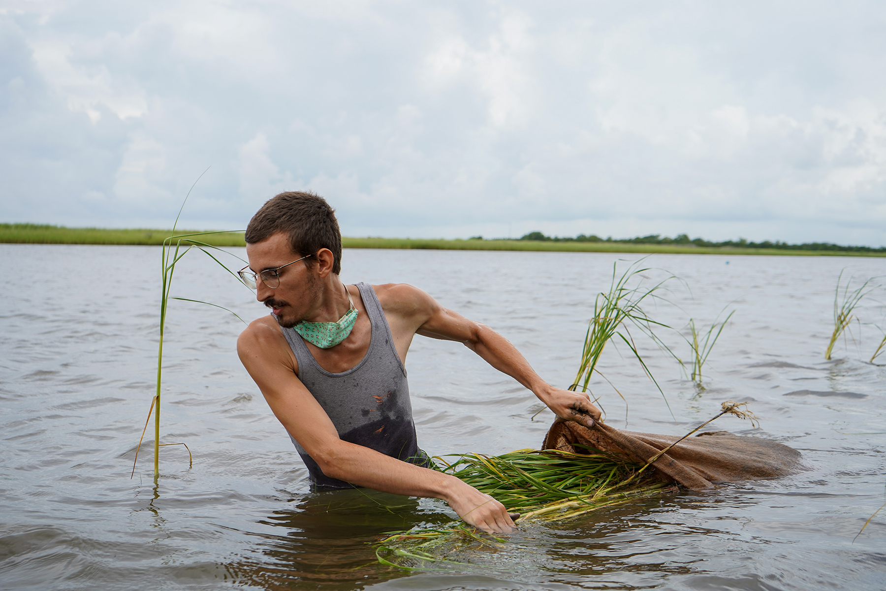AmeriCorp volunteer Calin Pons (they/them), 26, from State College, Pennsylvania, pulls a bag of grass plugs through the water.