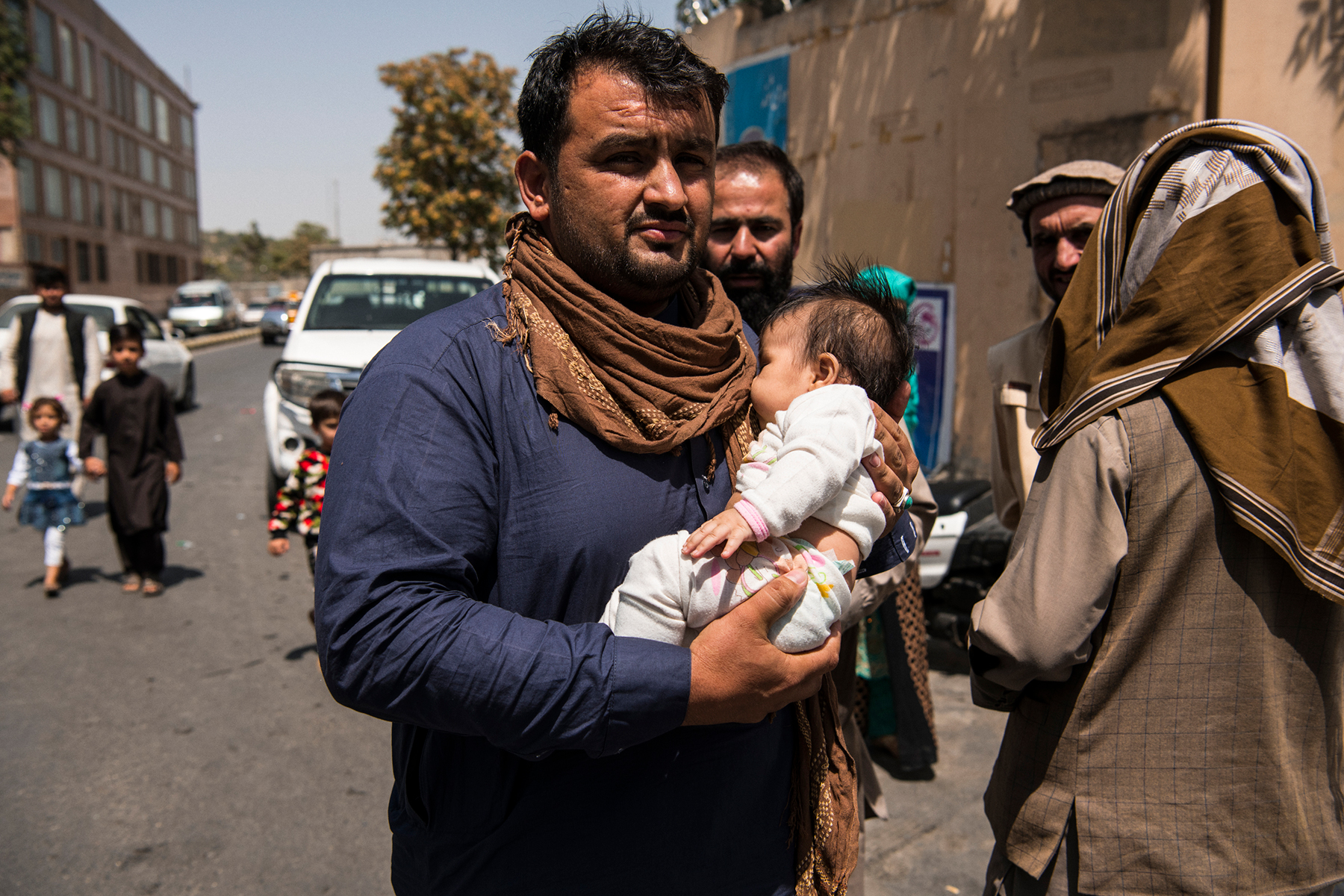 Agence France Presse Photographer Noorullah Shirzada carries his infant child inside Kabul's green zone in order to be transported to the international airport for evacuation flights. Yesterday, an agreement was reached by the Taliban leadership and the Afghan Government which saw President Ashraf Ghani step down in a transfer of power that saw barely any blood shed in the takeover of the capital. The takeover of the country transpired rapidly after U.S. and international forces began their final military from Afghanistan on May 1 this year. Since then, the Taliban swarmed across the countryside and then, ultimately, in early August, began overrunning provincial capitals, taking all 34 in a period of ten days, including Kabul, which they had surrounded by early this morning. The Taliban leadership instructed their fighters not to enter the city, though some appeared not to have received that order, parading through the streets on motorcycles and in Toyota Corollas. Government security forces were also asked to maintain security in the capital until further arrangements were made. By the afternoon most members of the government's security forces had shed their uniforms and most had left their posts, leaving somewhat of a power vacuum.