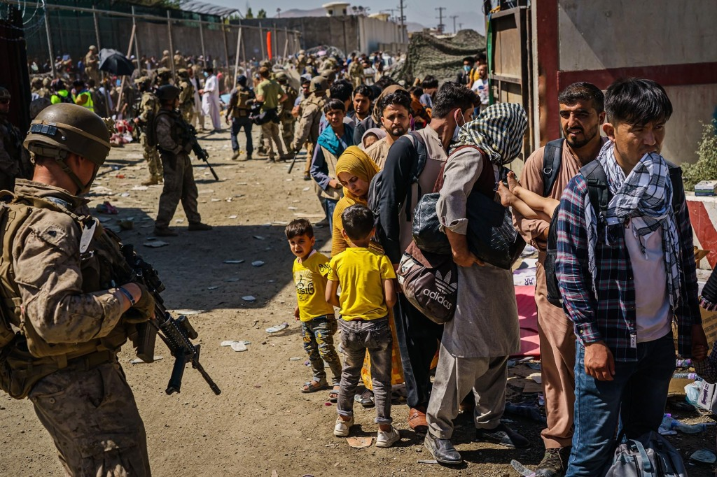 KABUL, AFGHANISTAN -- AUGUST 25, 2021: American soldiers watch over Afghan refugees waiting in line to be processed for an exit flight out of Kabul, Afghanistan, Wednesday, Aug. 25, 2021. (MARCUS YAM / LOS ANGELES TIMES)