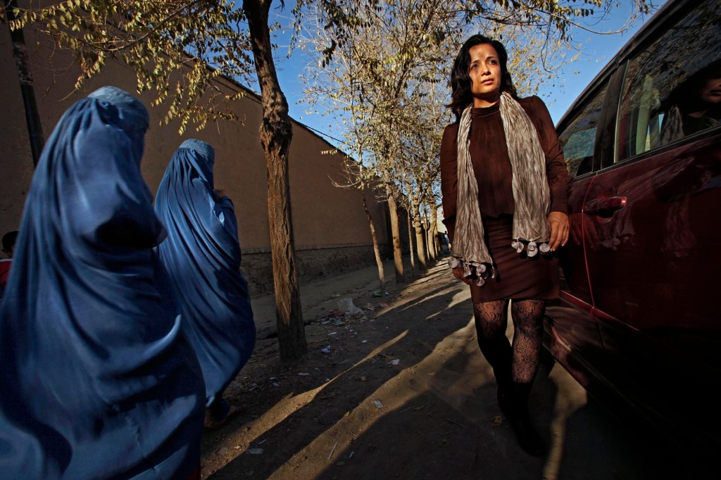 """Women in burkas stare at Fereshta with her bare legs and uncovered head, in Old Kabul's Shar-e-Kohna neighborhood. Fereshta Kazemi visits the set of the drama series, """"Kocha-e-Ma"""" -""""Our Street,"""" in which she will soon star. (Photo by Carolyn Cole/Los Angeles Times via Getty Images)"""