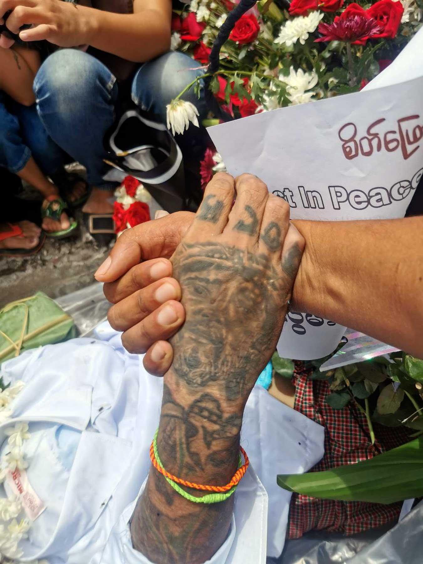 Novem Htoo holds the hand of Raymond at Raymond's funeral.