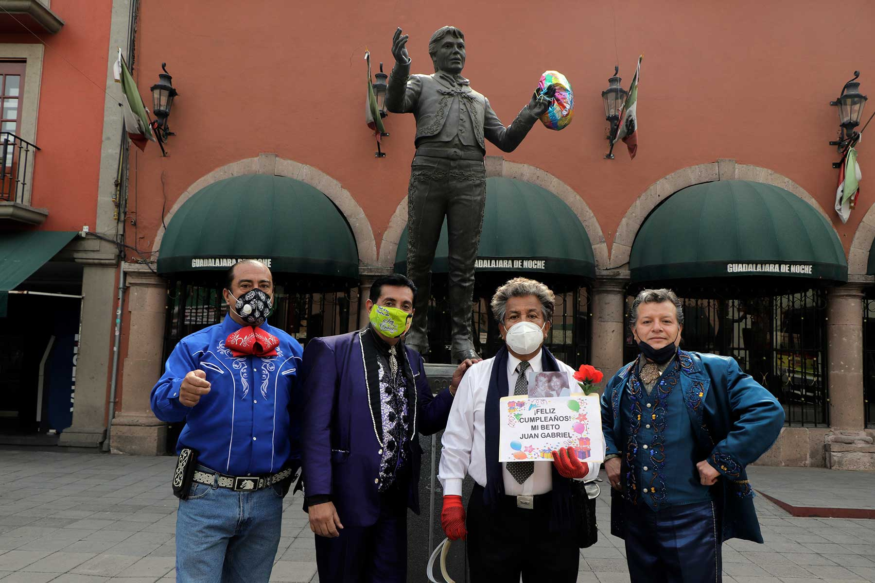 Followers of the singer, composer, songwriter and performer Alberto Aguilera Valadez, better known as Juan Gabriel, an icon of Mexican popular culture and music, pose in front of a statue in his honor at Plaza Garibaldi in Mexico City to pay tribute to him on the occasion of his birthday. However, this was not possible due to the epidemiological red traffic light for COVID-19 in the capital.  On Sunday August 28, 2016, Juan Gabriel, passed away in Santa Monica, California, United States. (Photo by Gerardo Vieyra/NurPhoto via Getty Images)