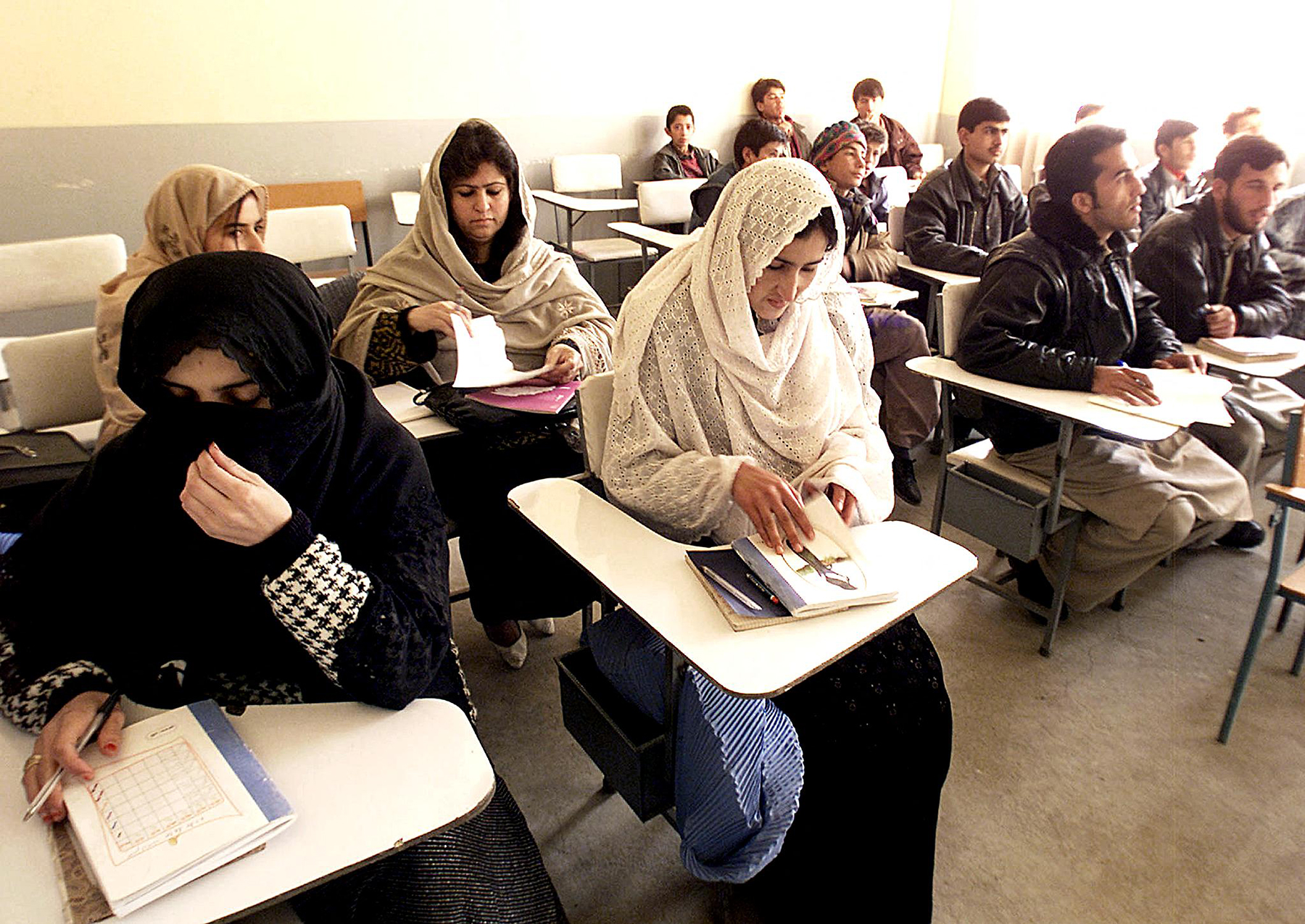 Afghan women sit as they study english in a class among male students in Kabul, 11 December 2001. Afghan women were not allowed to work out side home and study during the five years of the Taliban. Efforts are being made for more women rights after the fundamentalist regime of the Taliban collapsed 13 November. AFP PHOTO/Weda (Photo by WEDA / AFP) (Photo by WEDA/AFP via Getty Images)