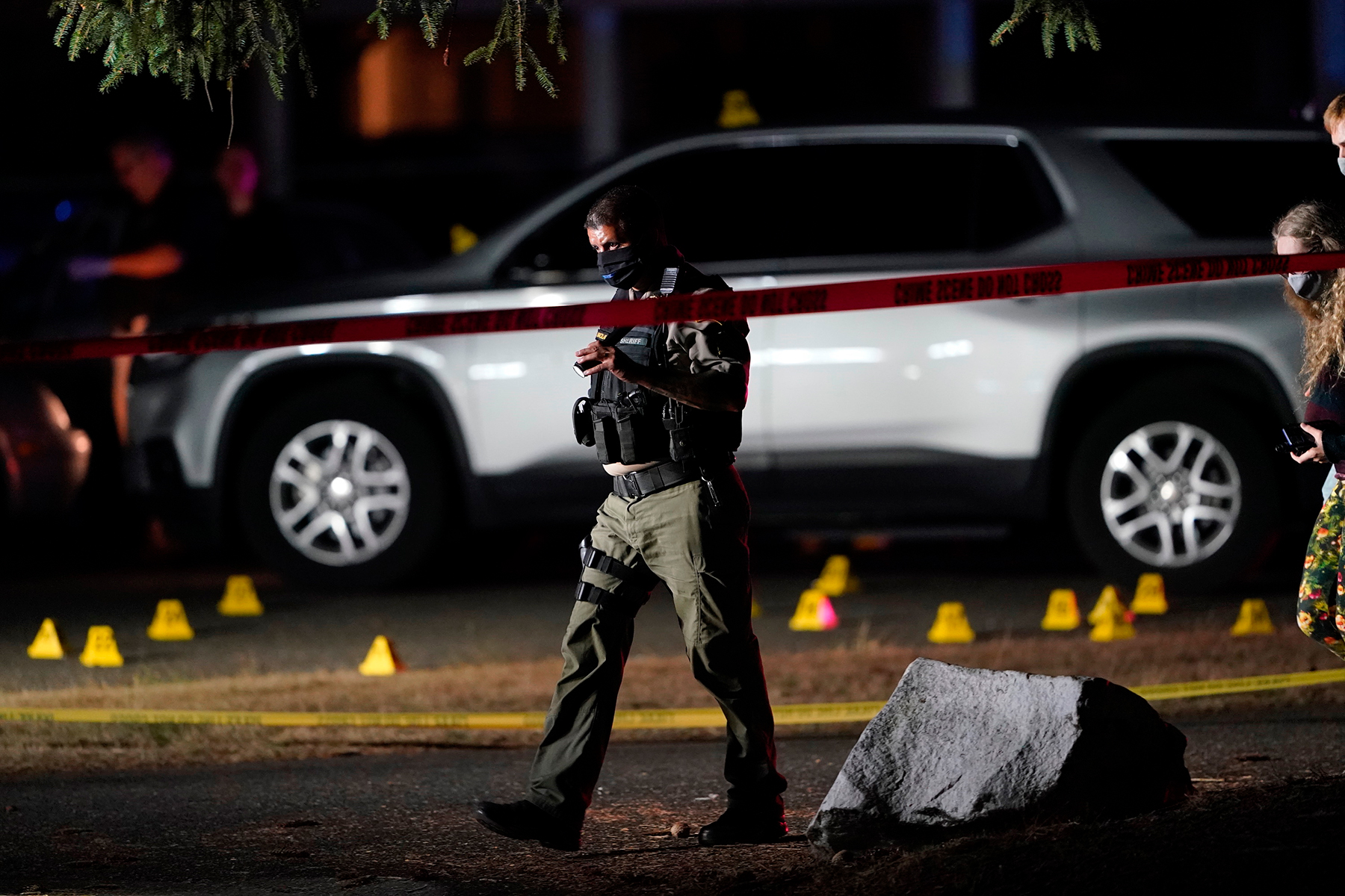 """Police walk past evidence markers at the scene where a man suspected of fatally shooting a supporter of a right-wing group in Portland, Ore., last week was killed as investigators moved in to arrest him in Lacey, Wash., Thursday, Sept. 3, 2020. Michael Reinoehl, 48, was killed as a federal task force attempted to apprehend him, a senior Justice Department official said. Reinoehl was the prime suspect in the killing of 39-year-old Aaron """"Jay"""" Danielson, who was shot in the chest Saturday night, the official said. (AP Photo/Ted Warren)"""