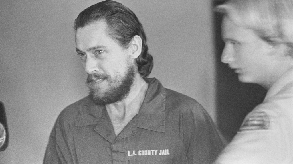 Porn star John Holmes, dressed in a prison jump suit, leaves Superior Court on his way back to the Los Angeles County Jail where he was released the day before. Holmes, jailed for nearly a year in connection with unsolved 1981 Laurel Canyon murders, earned his freedom by breaking his 111-day silence and telling the grand jury what he knew about the four bludgeoning slayings.