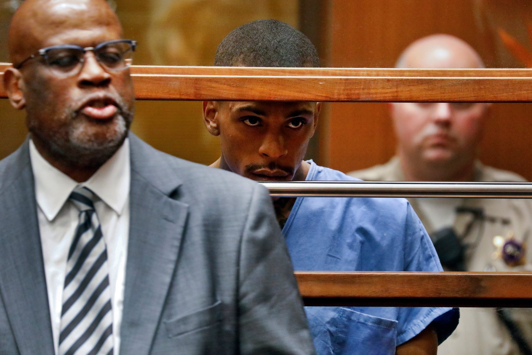 FILE - This April 4, 2019 file photo shows Eric Holder, the suspect in the killing of rapper Nipsey Hussle in Los Angeles County Superior Court with his attorney Christopher Darden, left. Holder is charged with murder and two counts of attempted murder in connection with the attack outside Hussle's The Marathon clothing store on March 31, 2019. A year after Hussle's death, his popularity and influence are as strong as ever. He won two posthumous Grammys in January, he remains a favorite of his hip-hop peers and his death has reshaped his hometown of Los Angeles in some unexpected ways. (Patrick T. Fallon/Pool via AP, File)