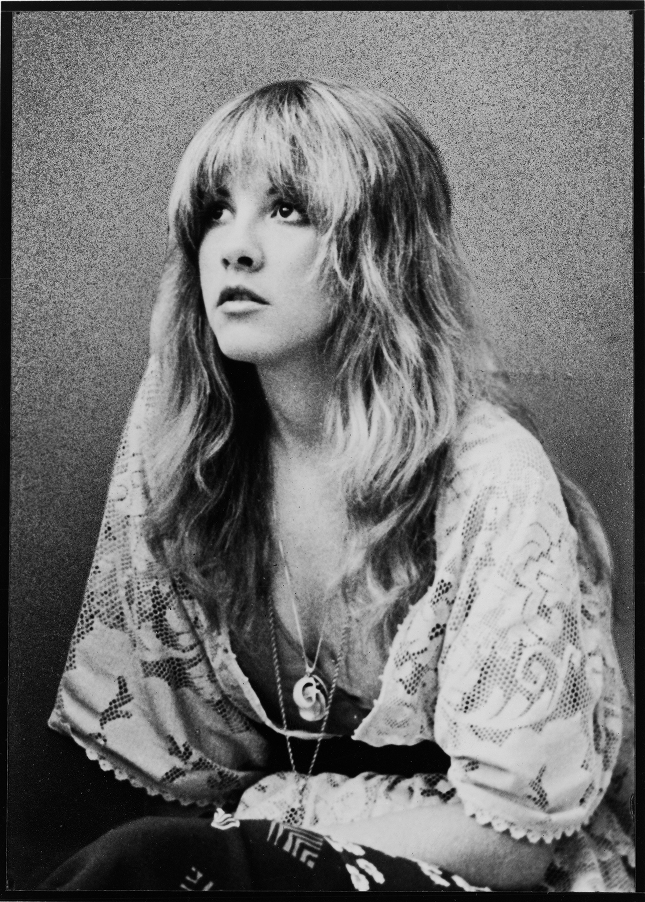 Promotional portrait of American pop and rock singer Stevie Nicks (of the group Fleetwood Mac) as she sits and looks upward, dressed in a lace shawl, late 1970s. (Photo by Hulton Archive/Getty Images)