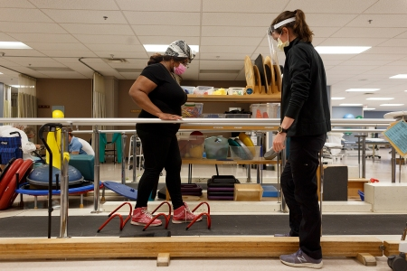 """Heather-Elizabeth Brown, left, works on her balance during a strengthening exercise while Dr. Sarah Knipper, right, encourages her on Tuesday, Aug. 18, 2020 at Beaumont Health and Wellness Center in Royal Oak, Mich. Brown contracted COVID-19 and spent 31 days on a ventilator and now suffers from multiple serious health issues due to the virus.""""Before I got it, I was doing everything I could do to not get it. If I do get it, maybe it won't be too bad? And when I did get it, it was the absolute worst,"""" said Brown."""