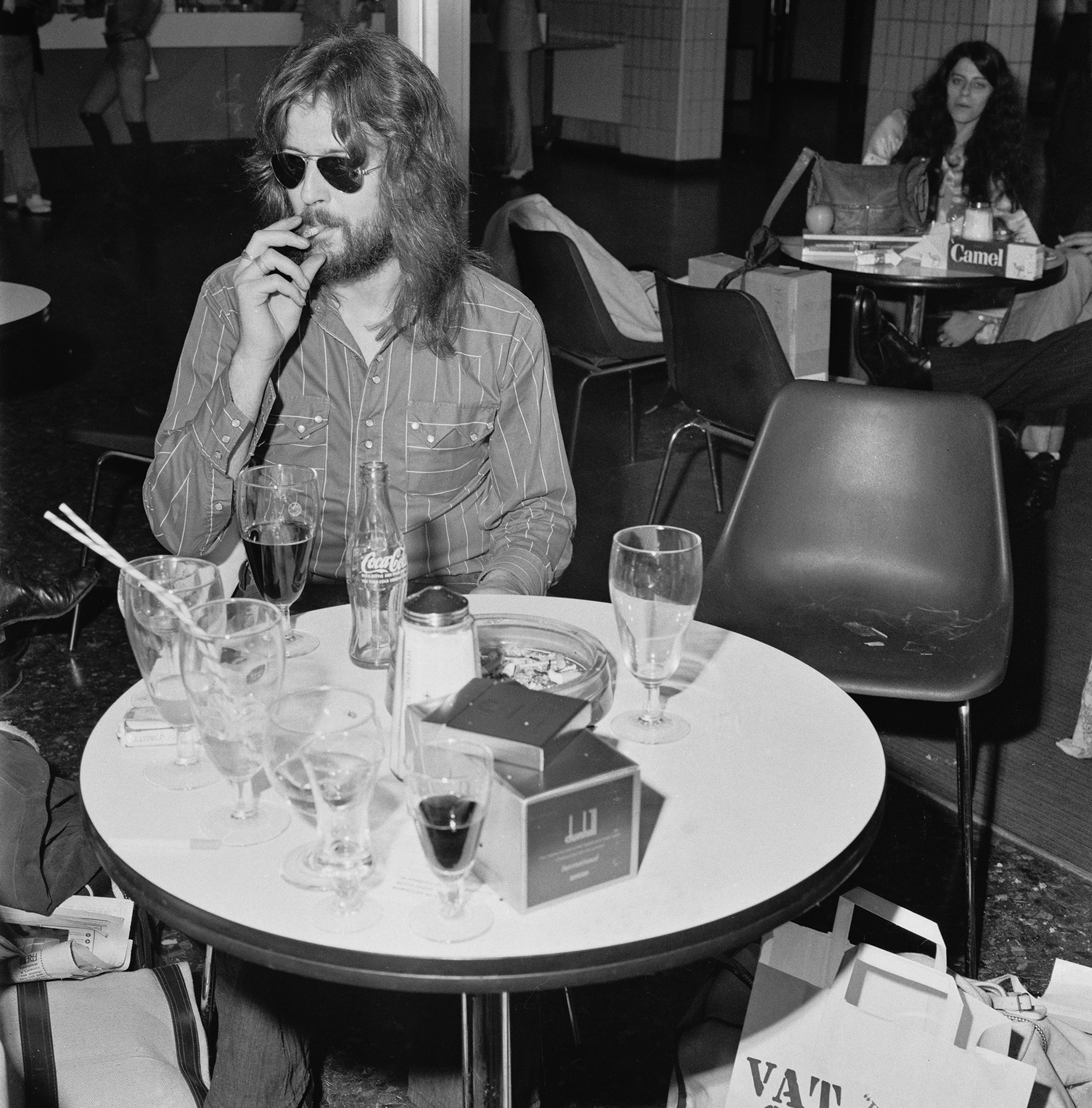 English musician, guitarist and singer Eric Clapton smokes a cigarette with a drink in an airport cafeteria in May 1971. Eric Clapton is preparing to fly to France to attend the wedding of Mick Jagger and Bianca Perez-Mora Macias. (Photo by Evening Standard/Hulton Archive/Getty Images)